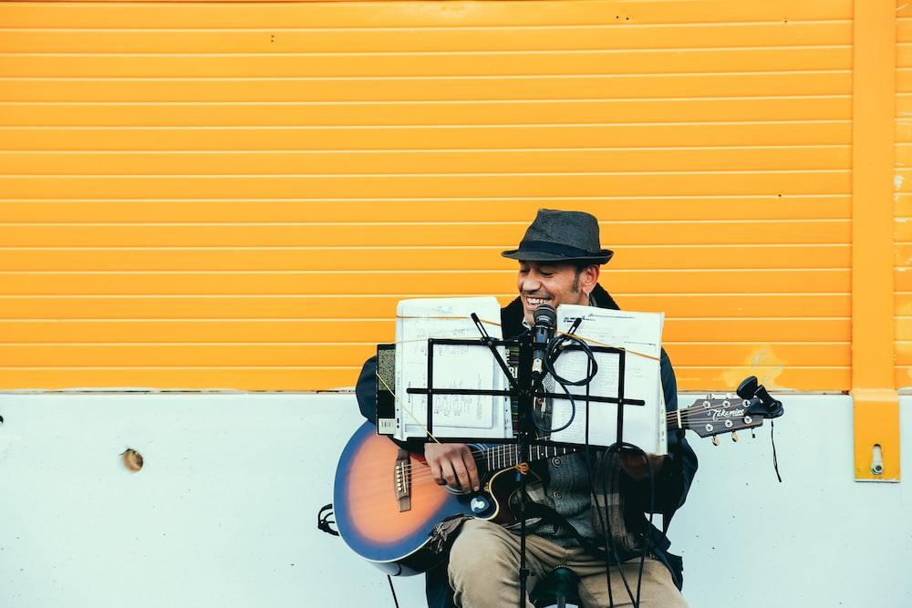 Hombre tocando guitarra acústica marrón y negra