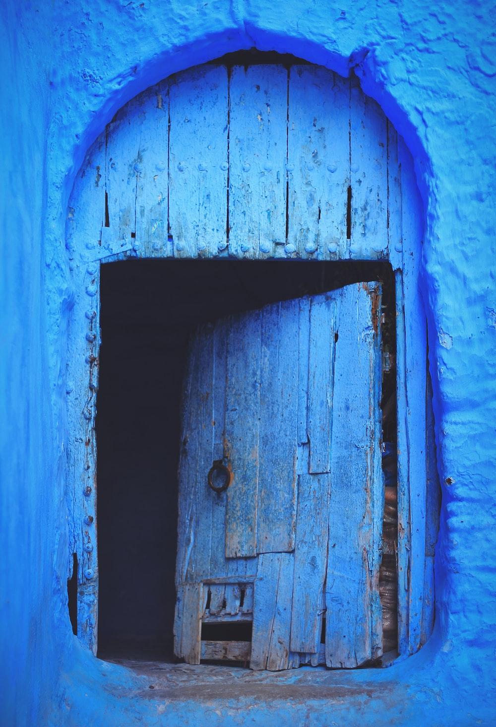 low light photography of blue wooden door