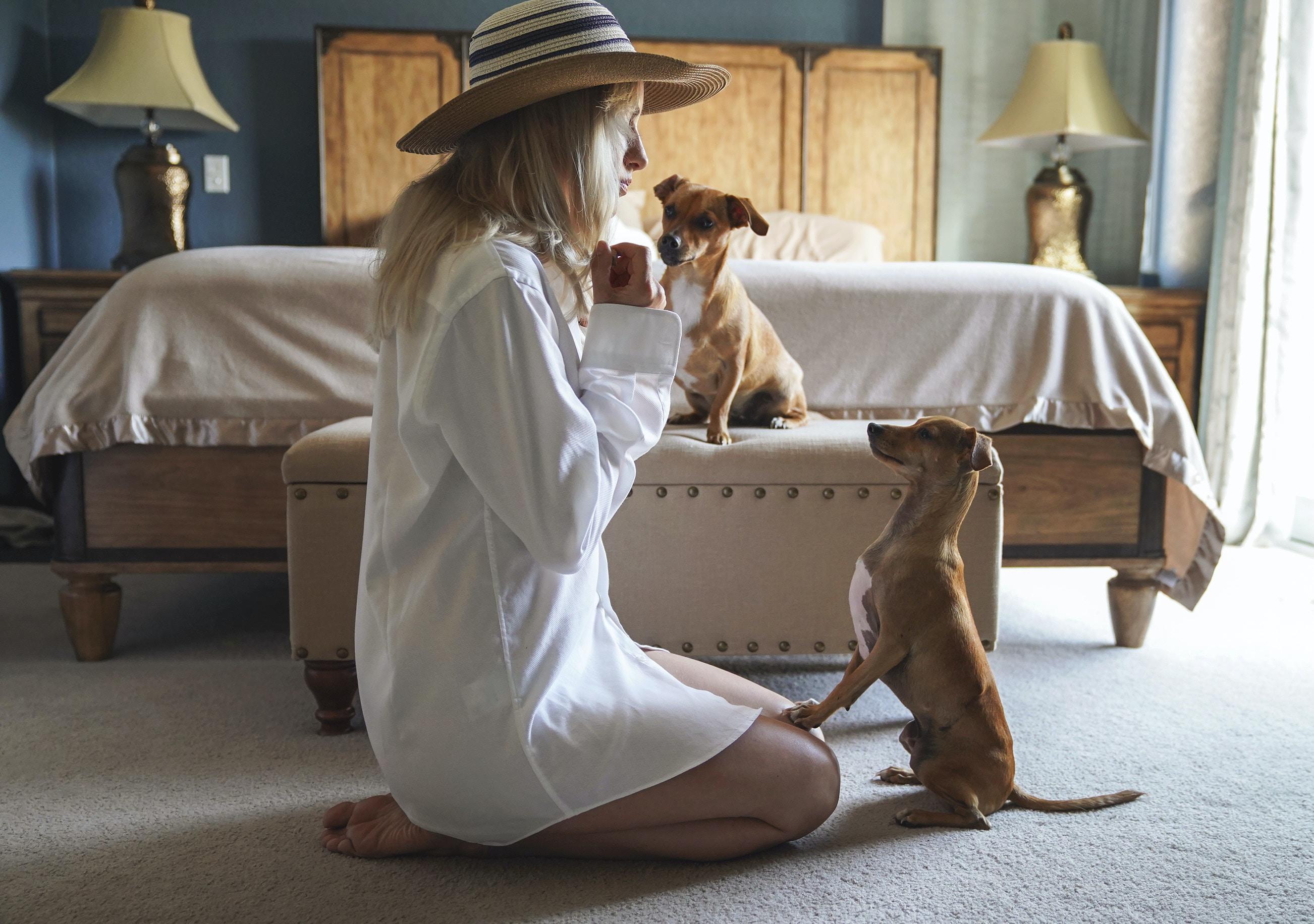woman sitting beside tan dog