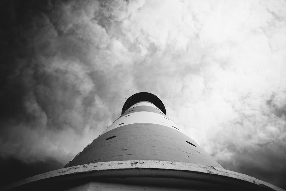 greyscale and low angle photography of lighthouse