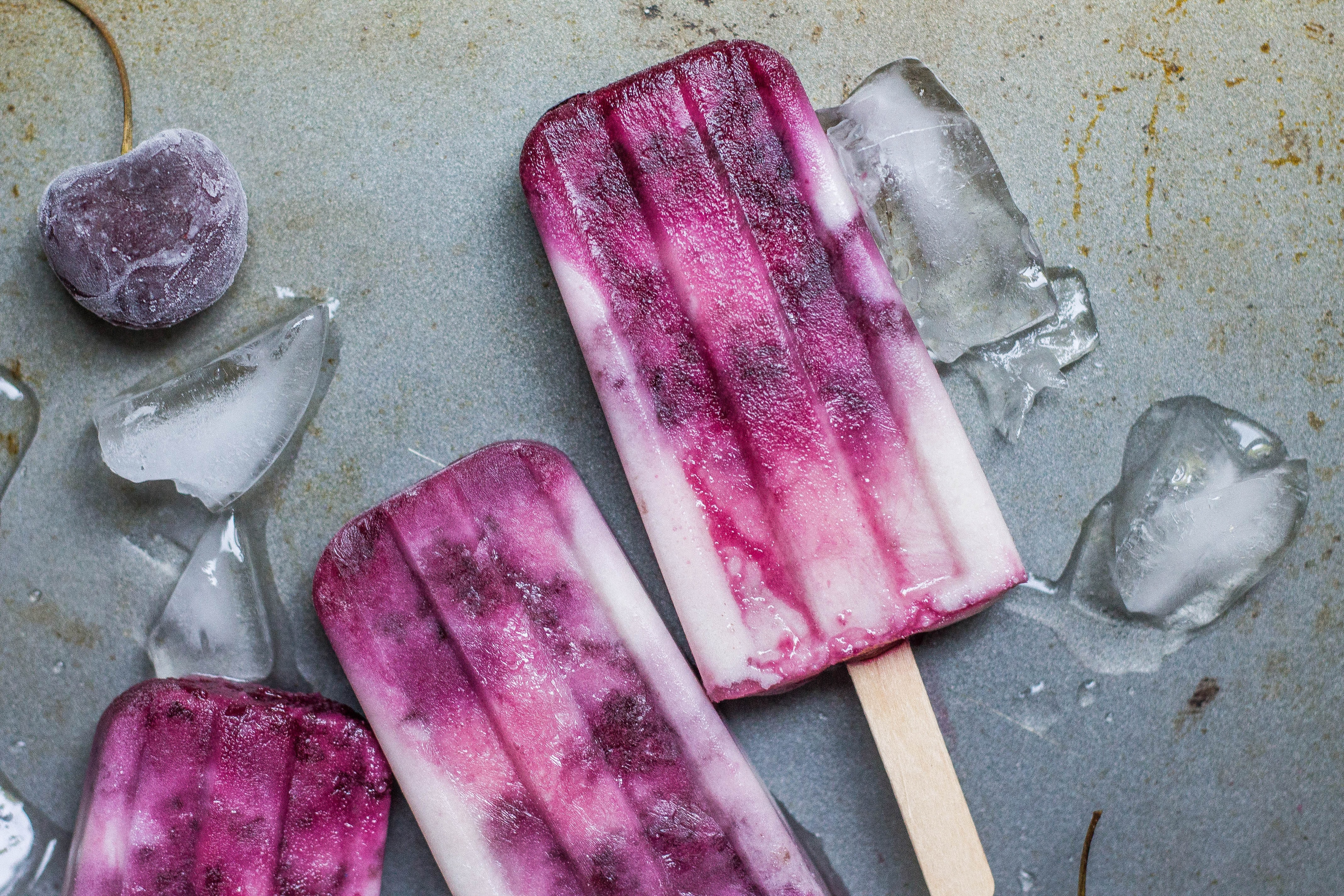 purple and white ice pop lying on wet ground with ice