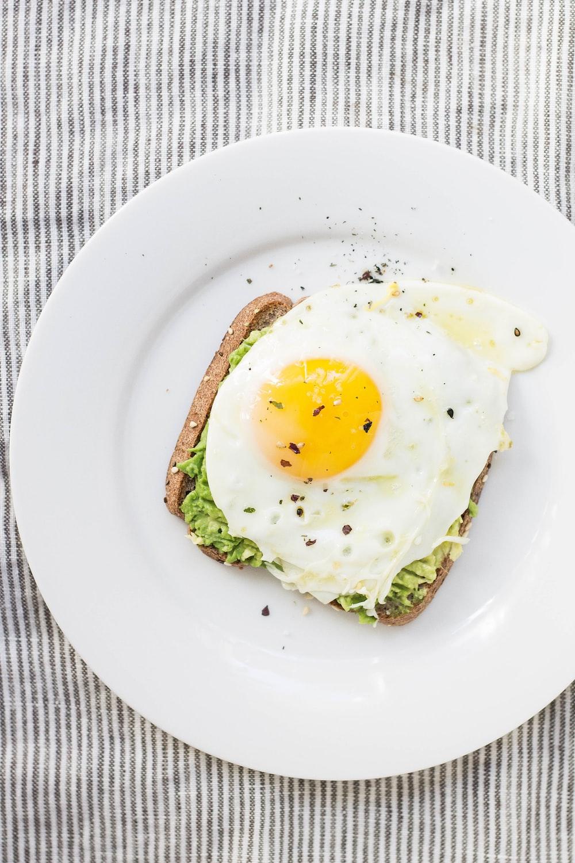 sunny side up egg, lettuce, bread on white ceramic plate