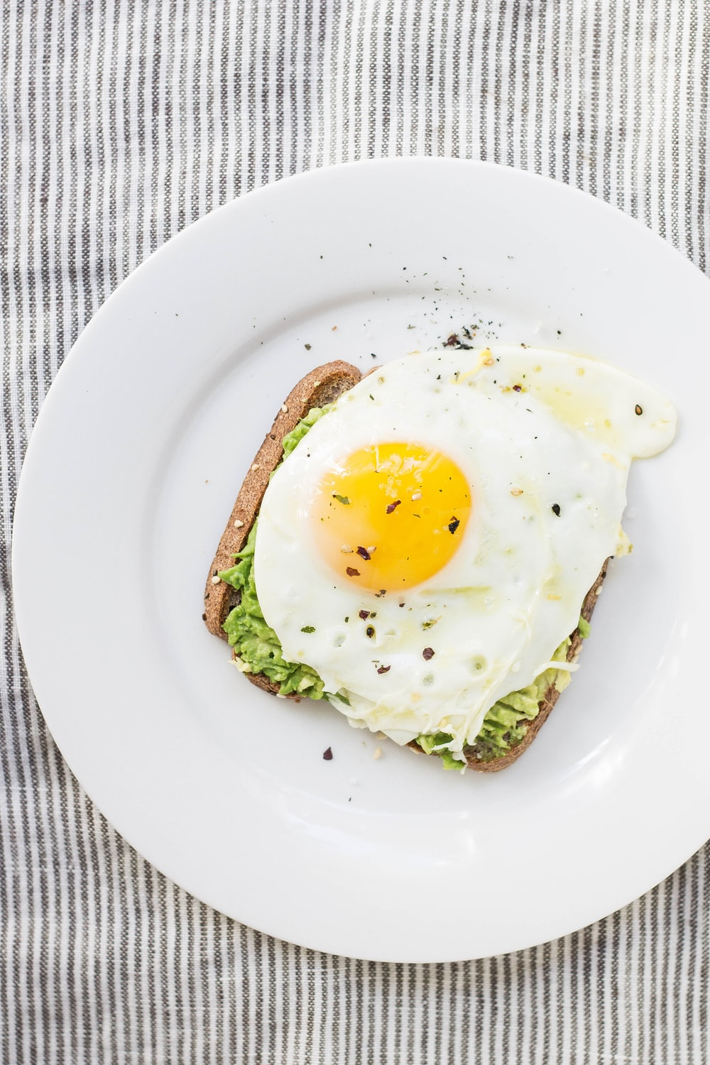 sunny side up egg, lettuce, bread on white ceramic plate