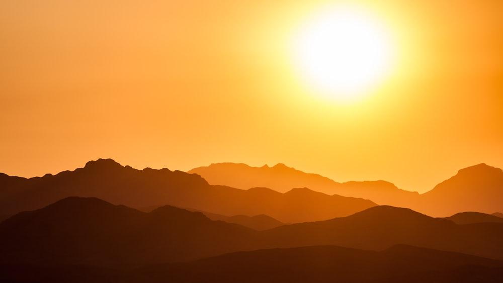 silhouette of mountains under orange sky