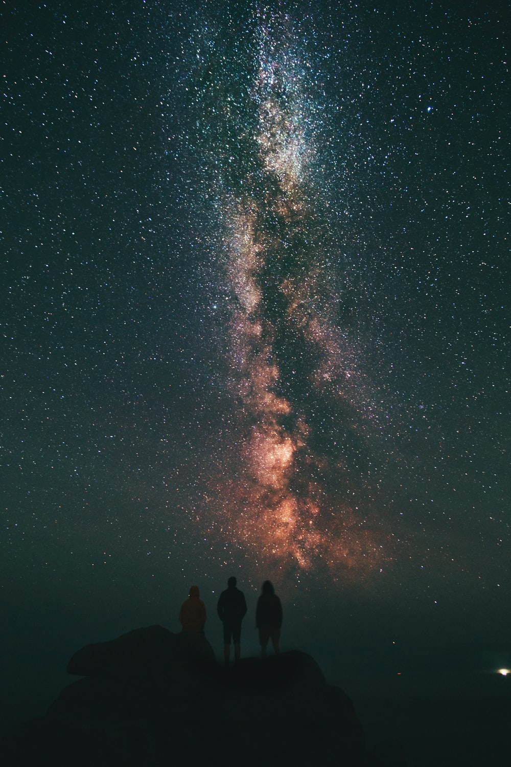three person looking stars and milky way