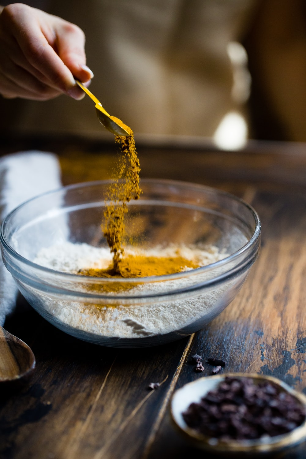 person pouring seasonings on clear glass bowl