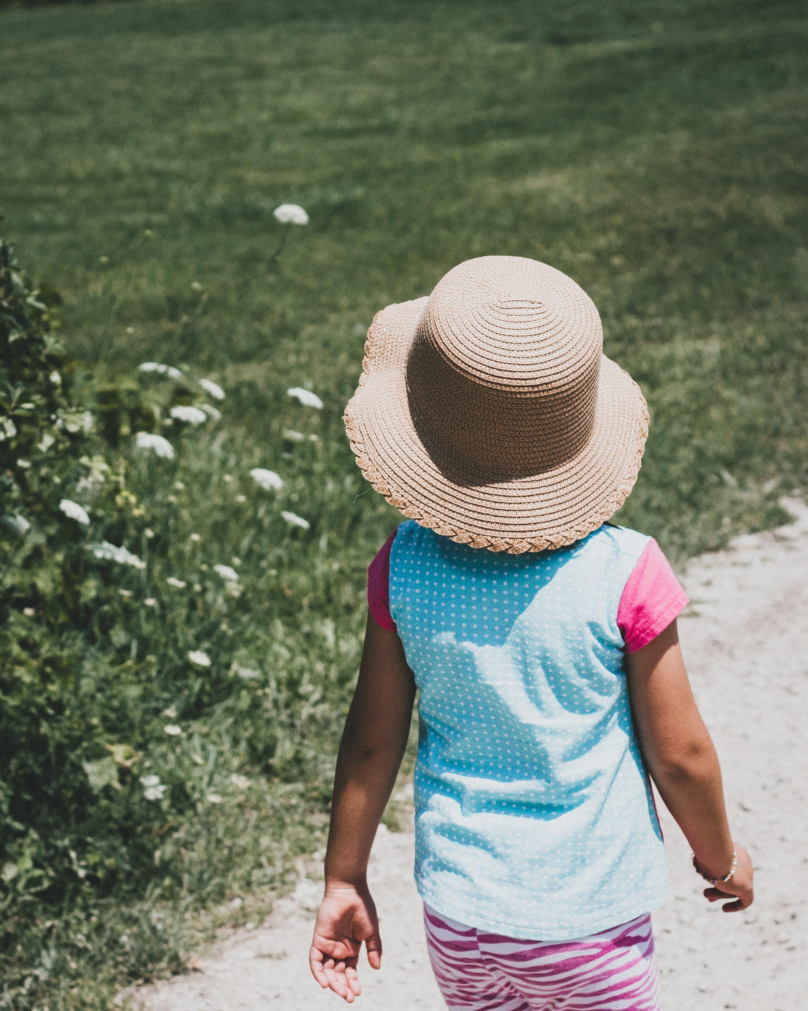 girl walking near green grass field