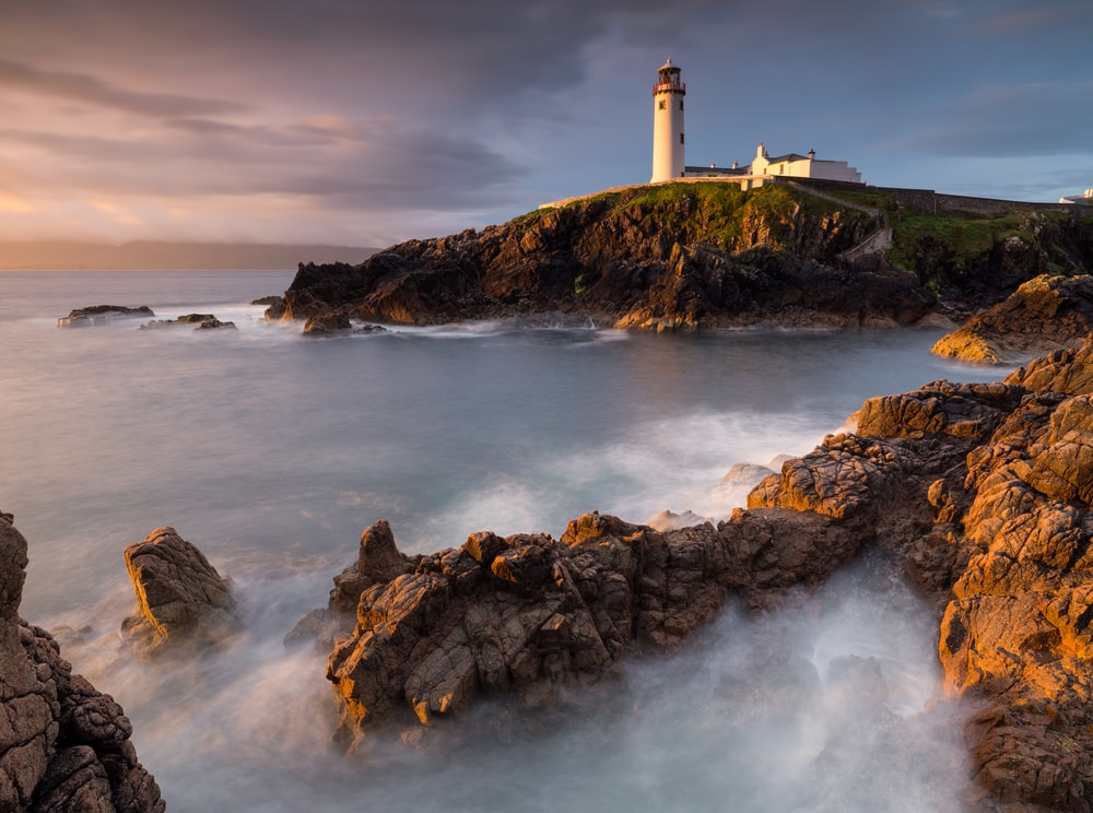 white lighthouse on hill during black clouds
