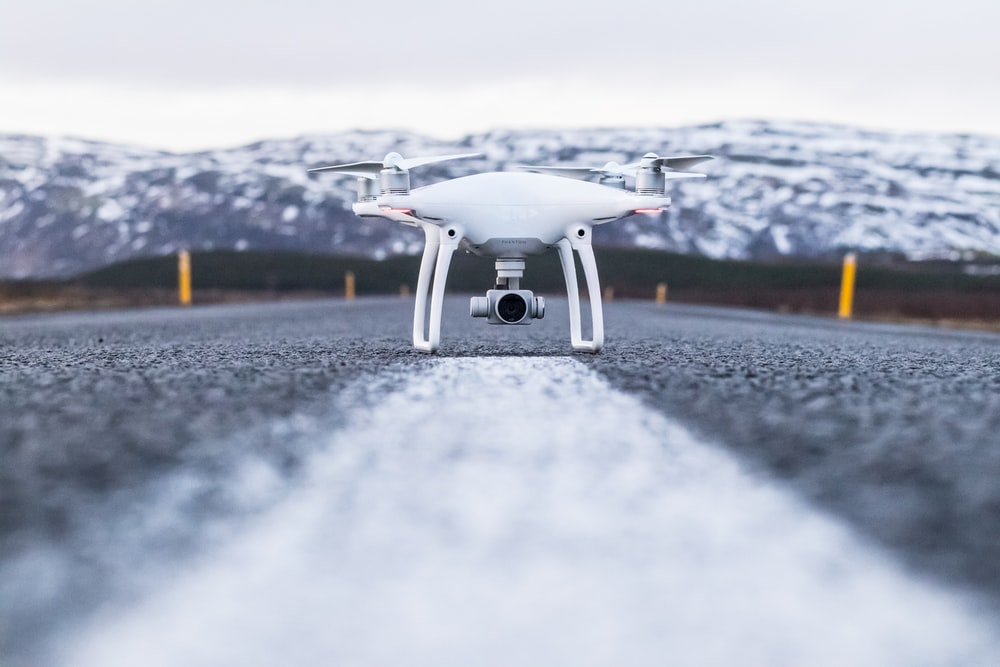 white quadcopter on gray concrete road top during daytime