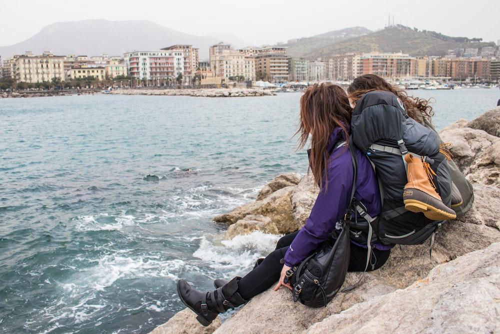 two girls sitting on large rocks watching waves crashing along rocks