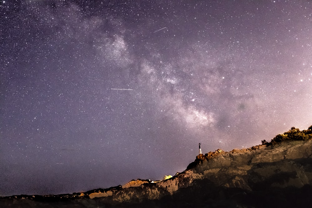 person standing on rock formation under starry sky