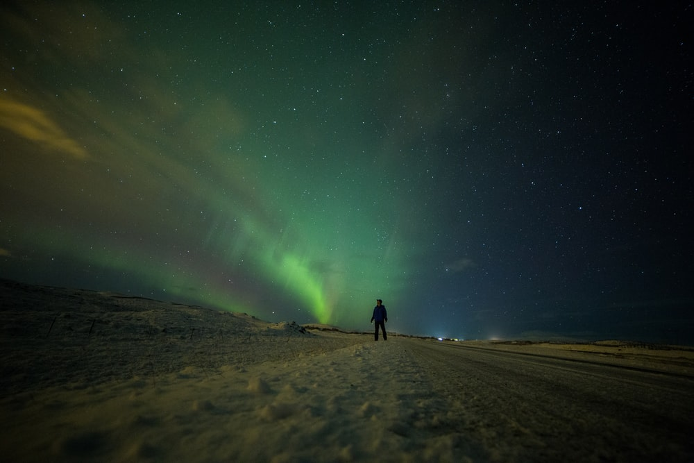 silhouette of person standing on brown sand under northern lights