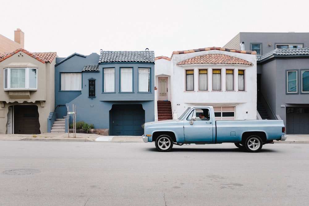 white single cab on road near blue and white houses