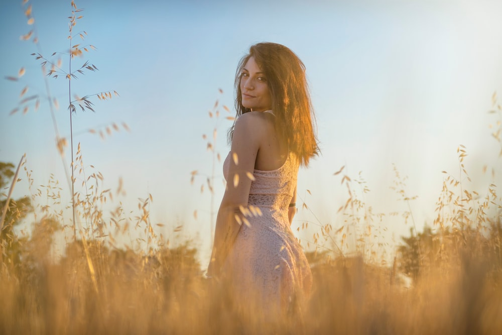 woman standing in the middle of brown grass