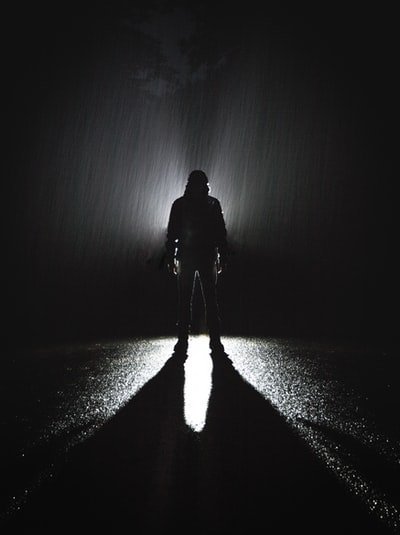 silhouette of person standing on road during rain