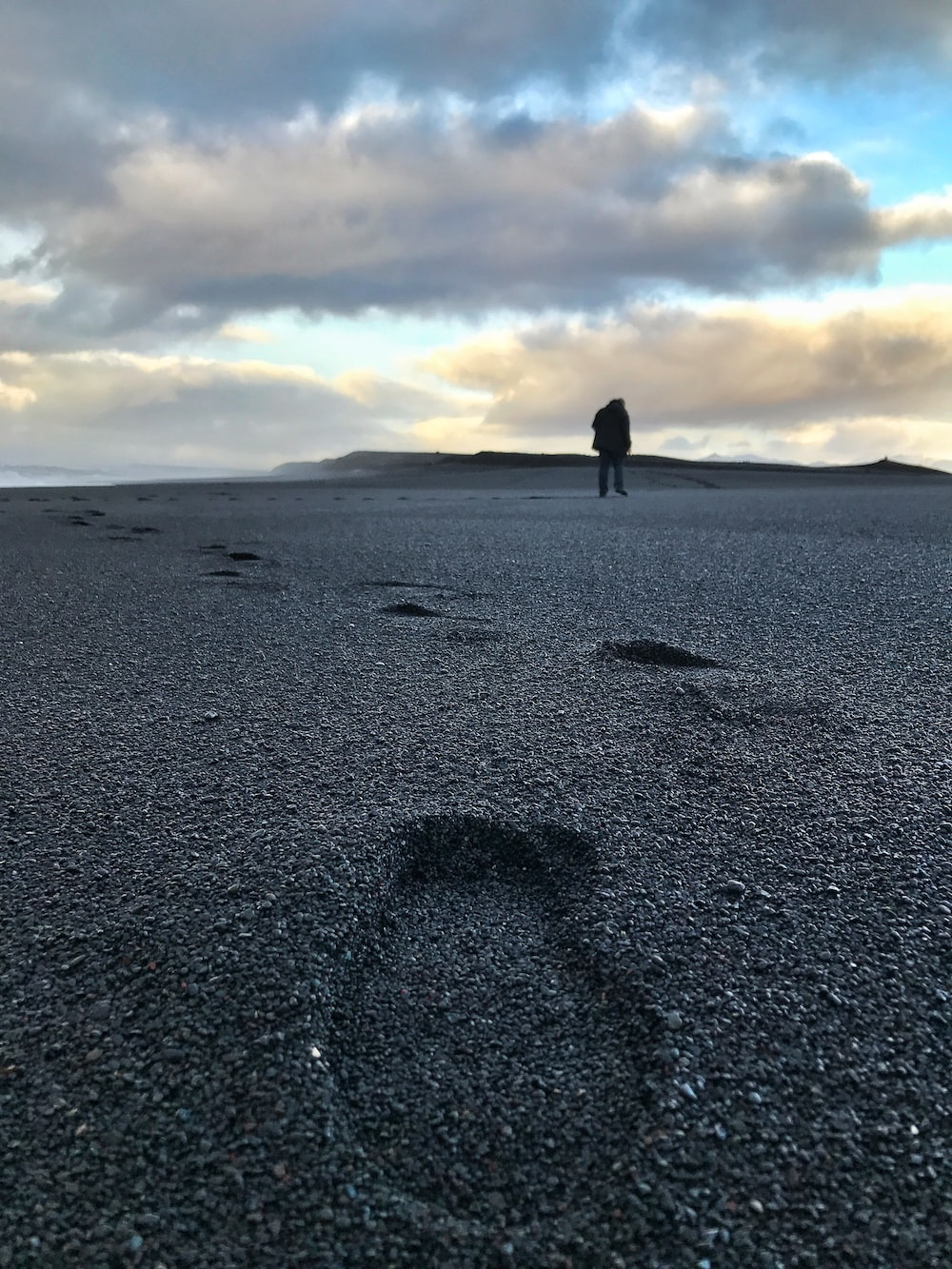 man standing on black sand