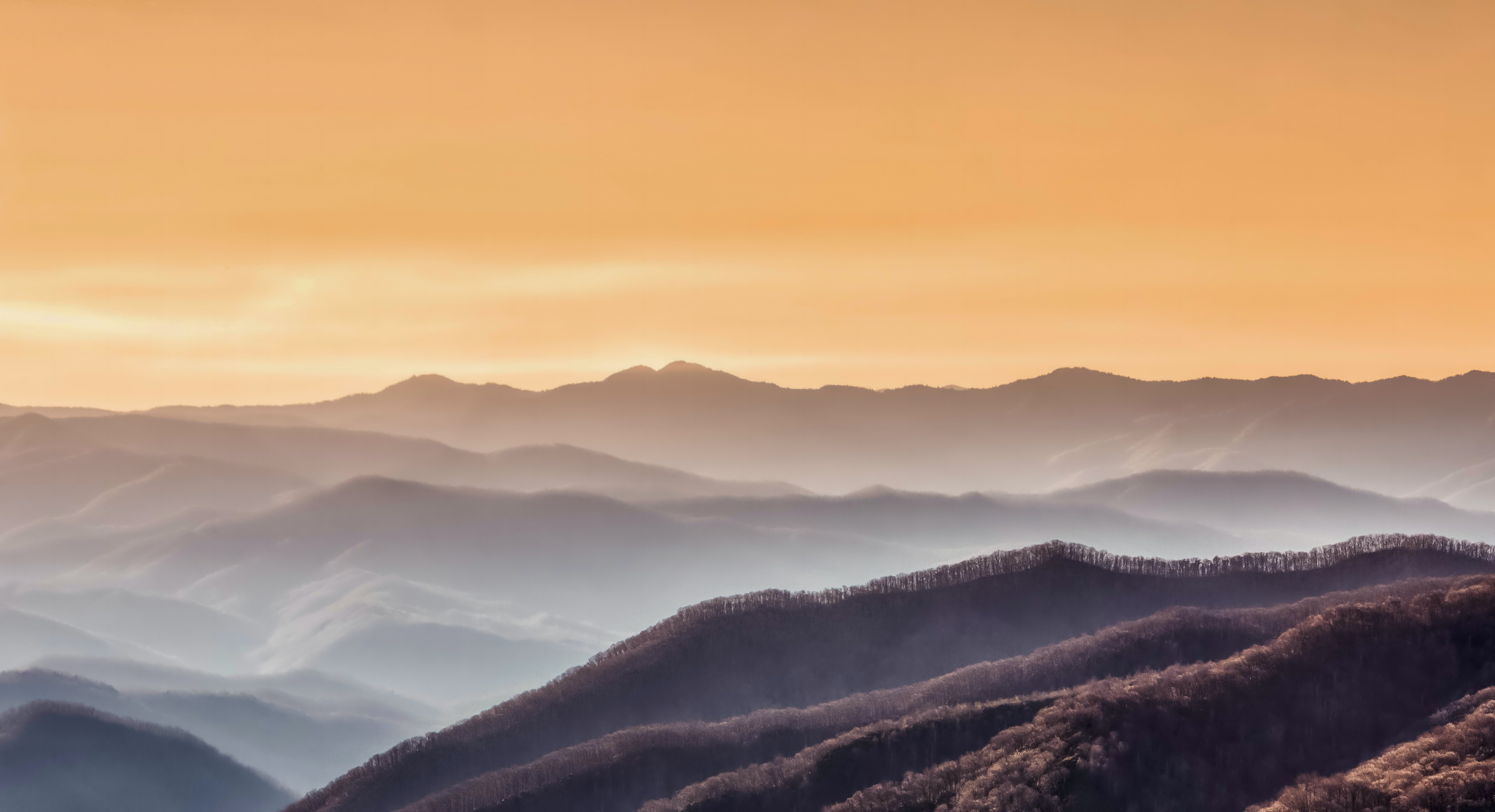 Fog covered mountains during sunset.