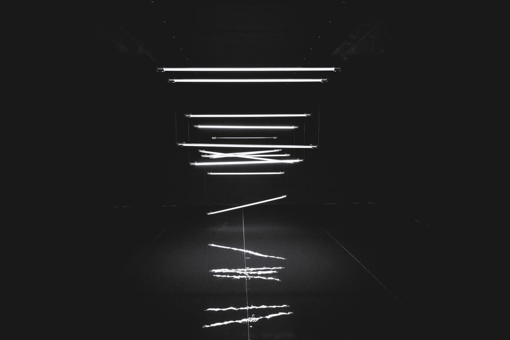 A unique shot of tube lights falling from the ceiling in a dark room.