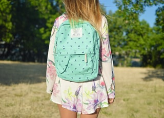 woman in white and multicolored floral long-sleeved mini dress with green backpack