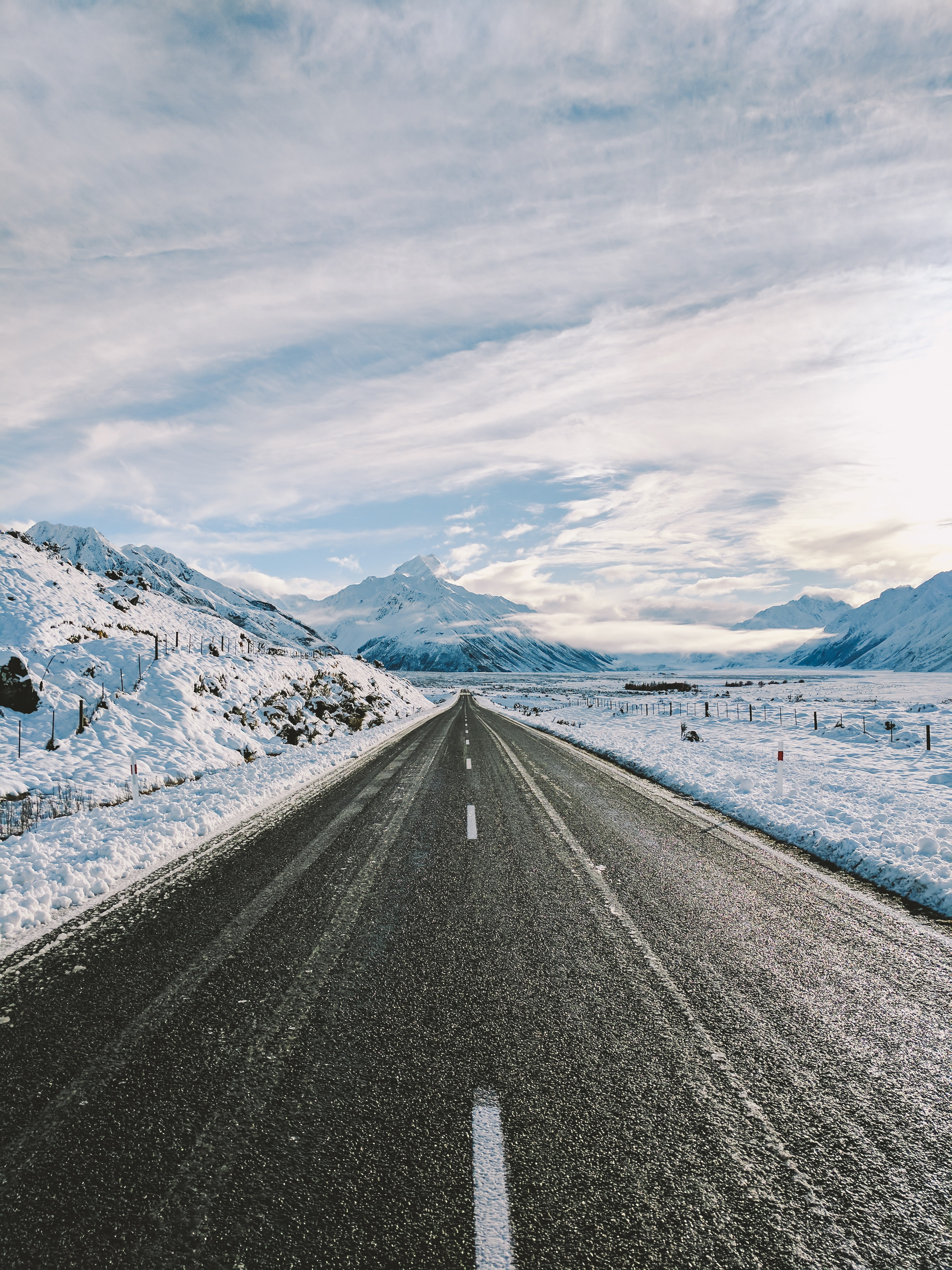 An empty road near snow covered mountains.