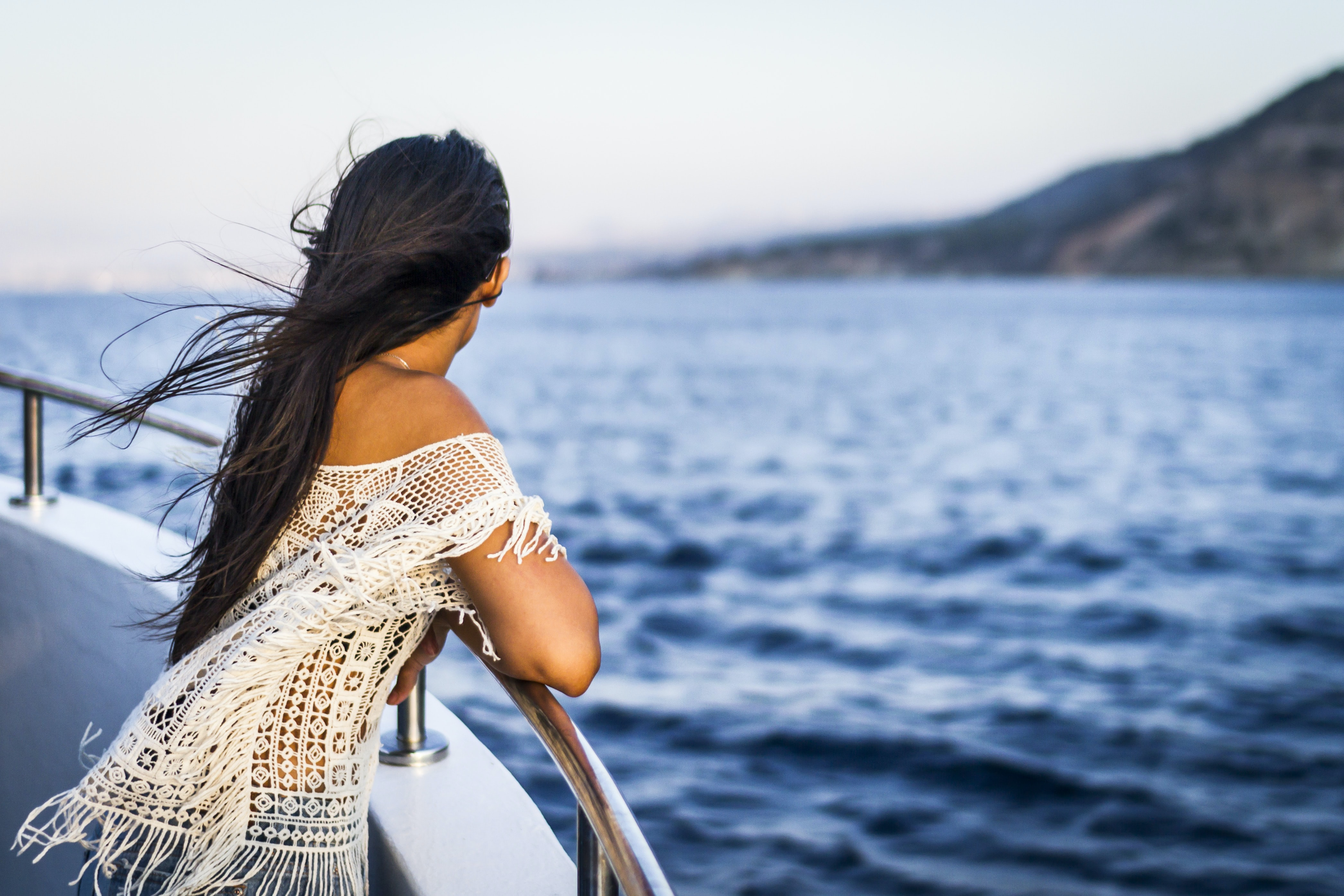 A woman staring out into the water while standing at the side of a boat.
