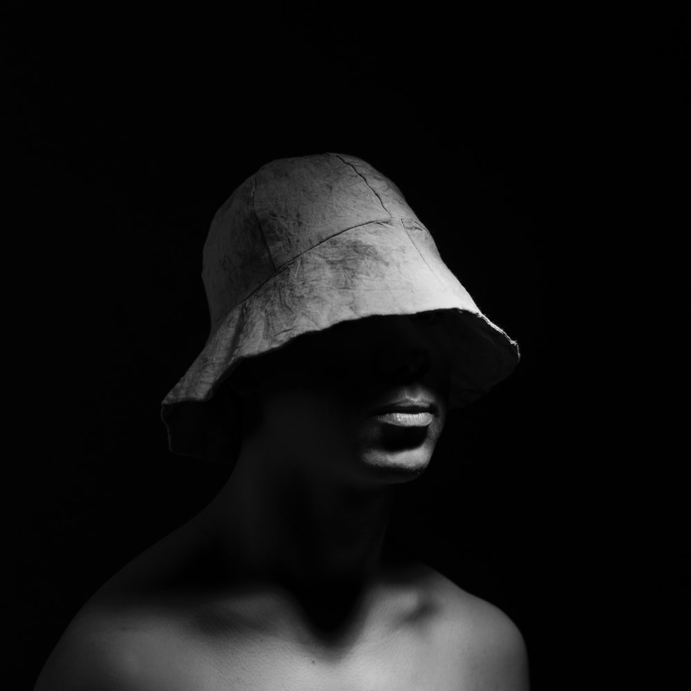 Grayscale photo of topless man wearing bucket hat