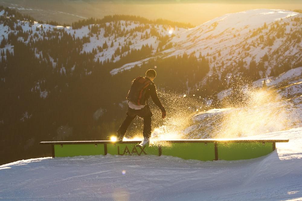 man riding ski on railings near mountain at daytime