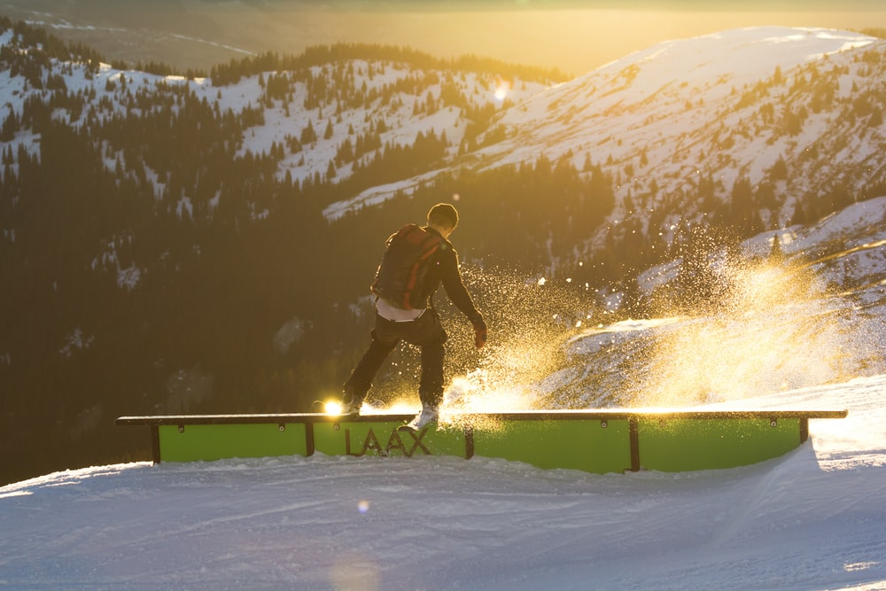 man riding ski on railings near mountain at daytime