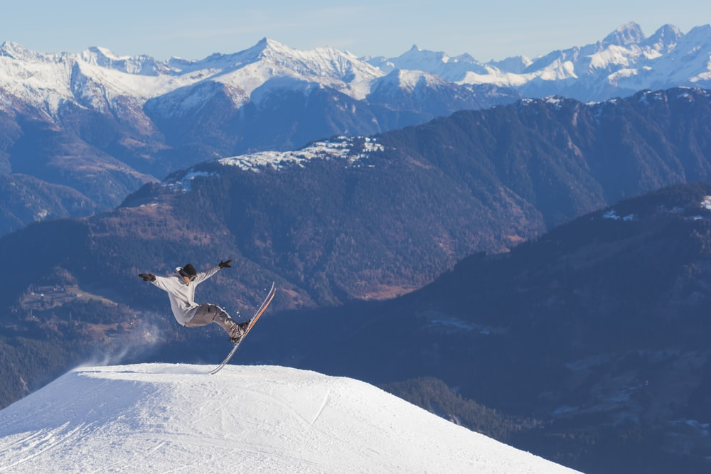 person in white long-sleeved shirt skiing during daytime