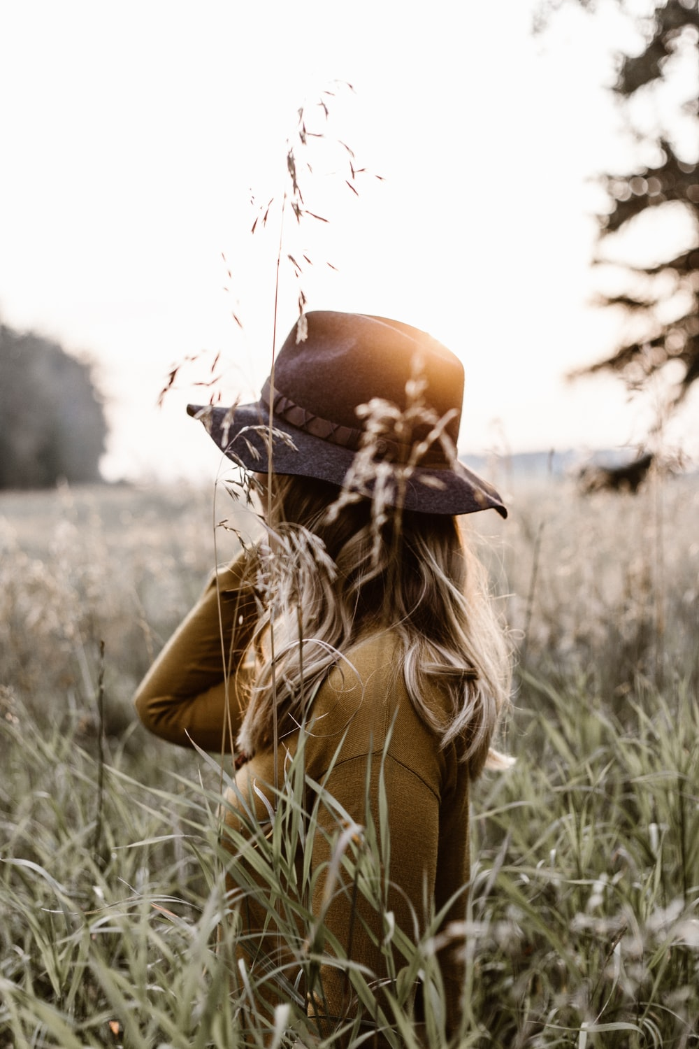 woman standing in middle of grasses