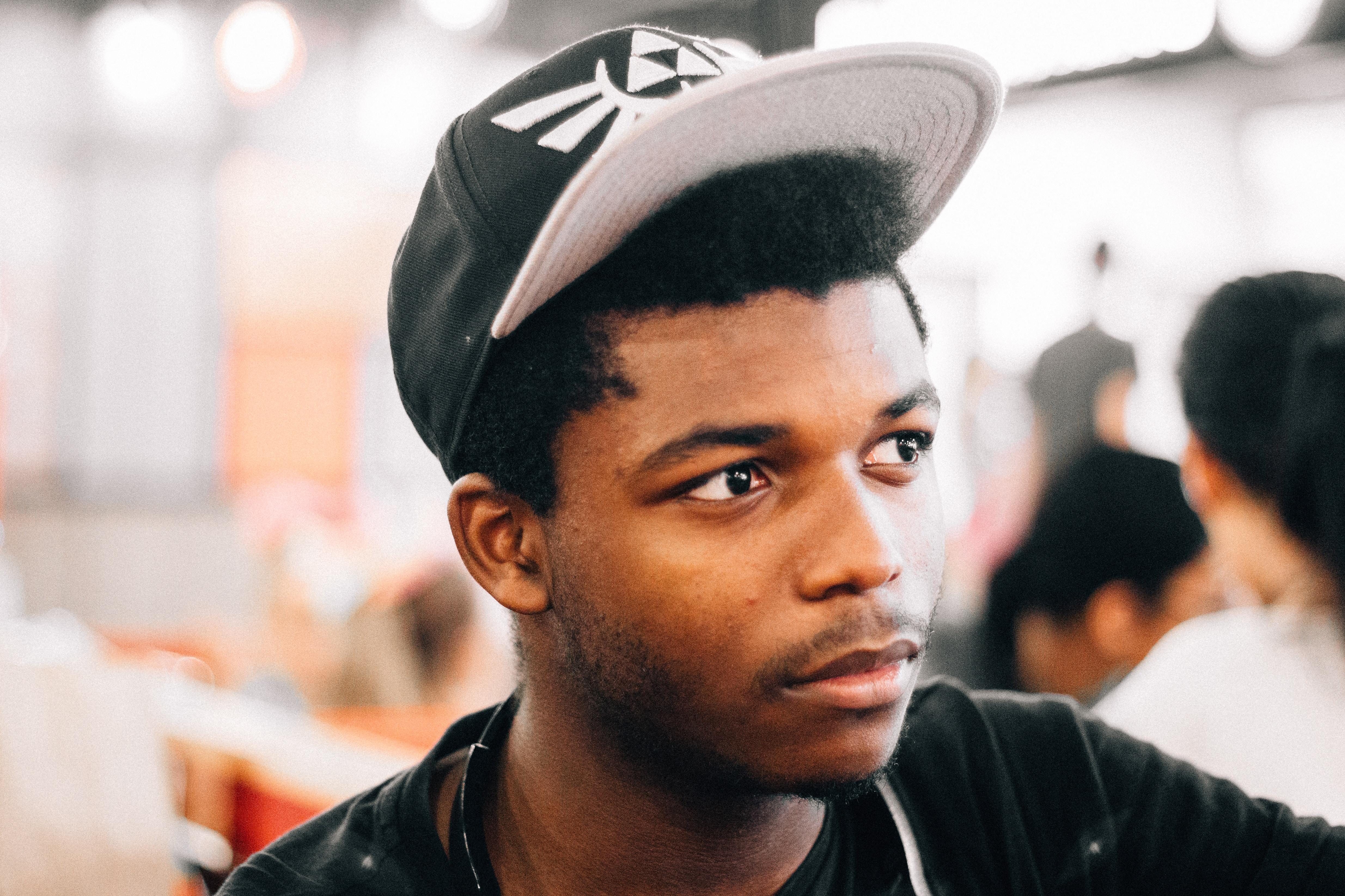 closeup photo of man wearing black and white cap