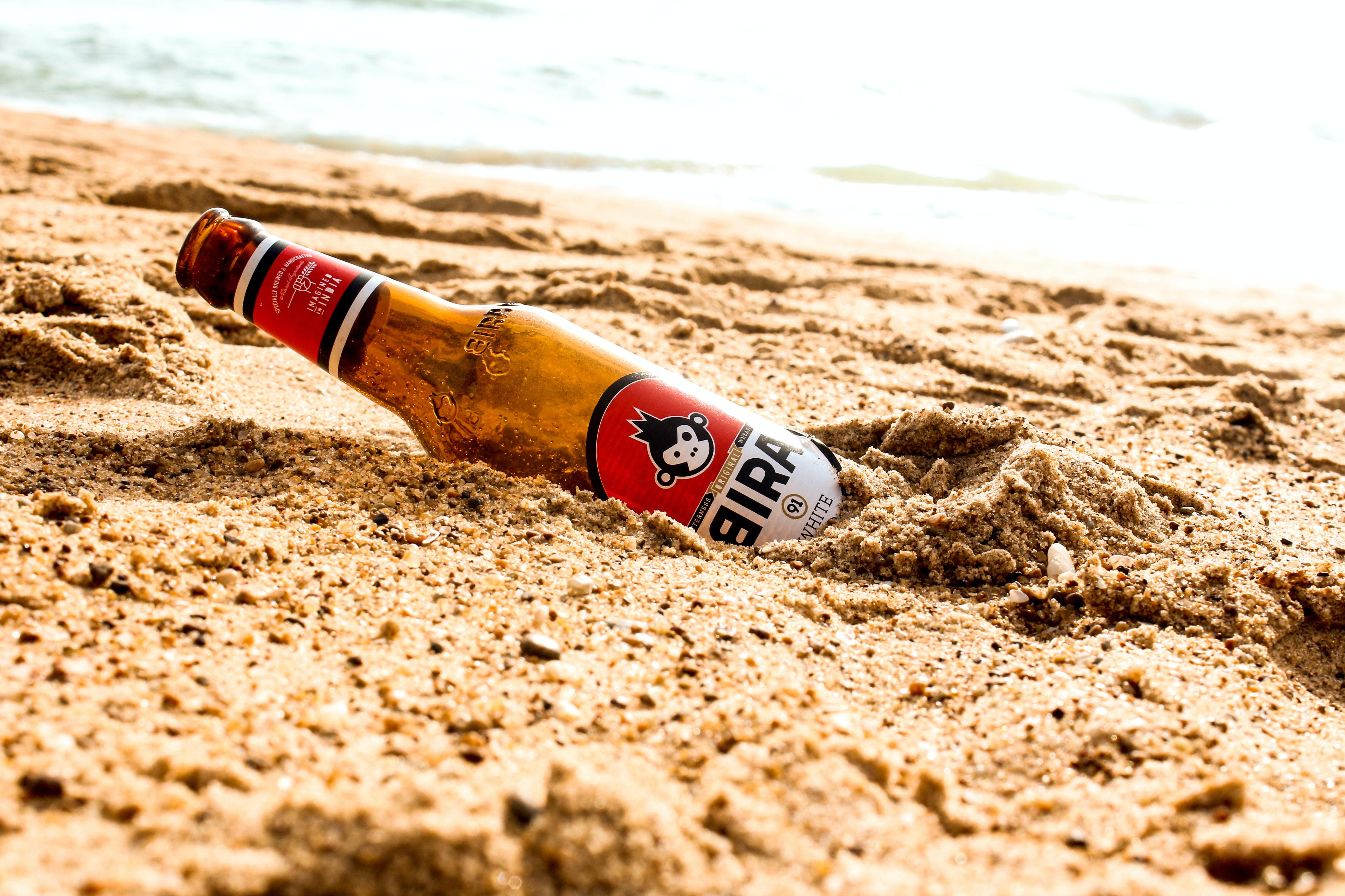 brown glass bottle over brown sands