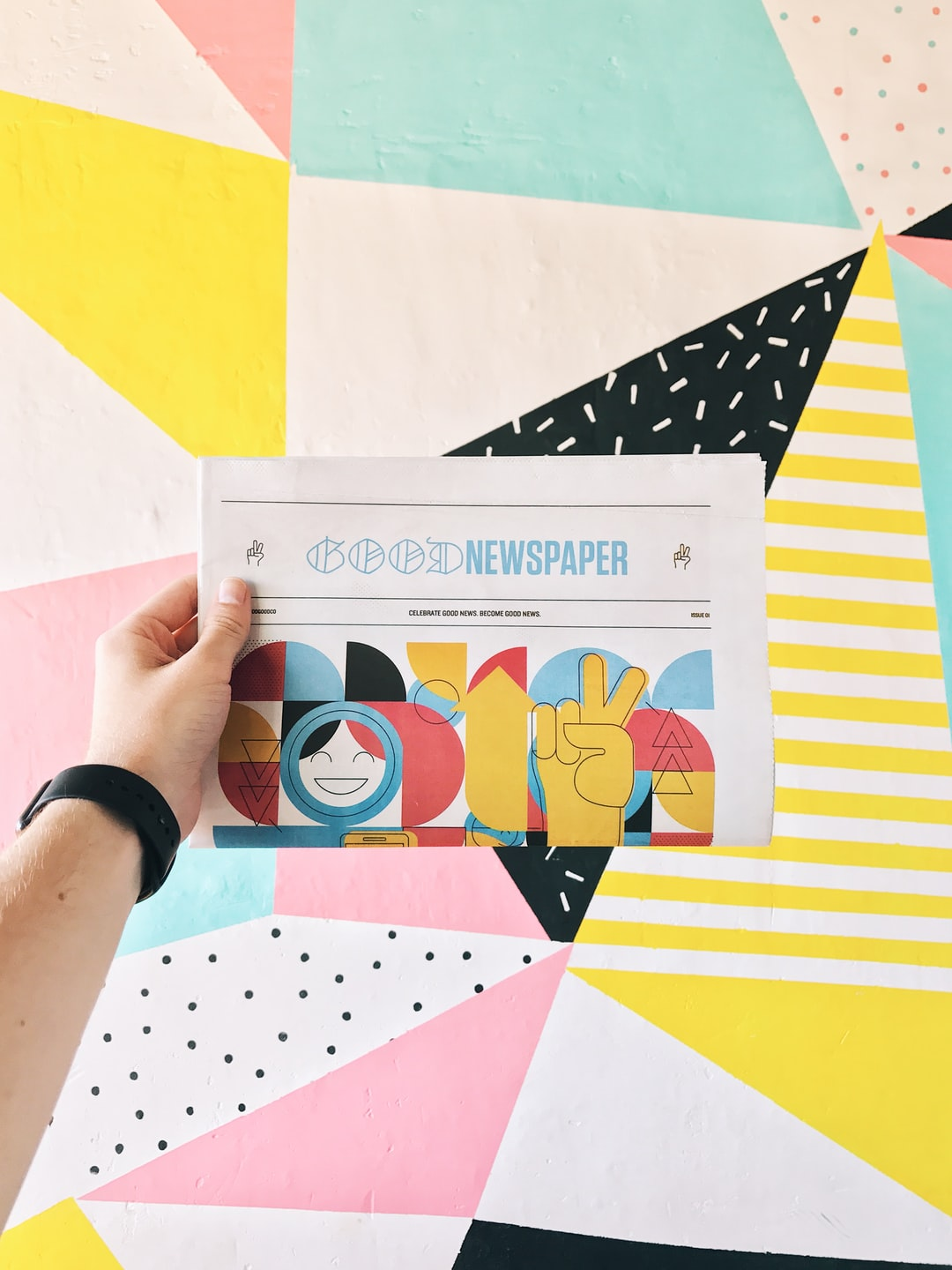 """A """"Good Newspaper,"""" being held up in front of an abstract, colorful patterned floor."""