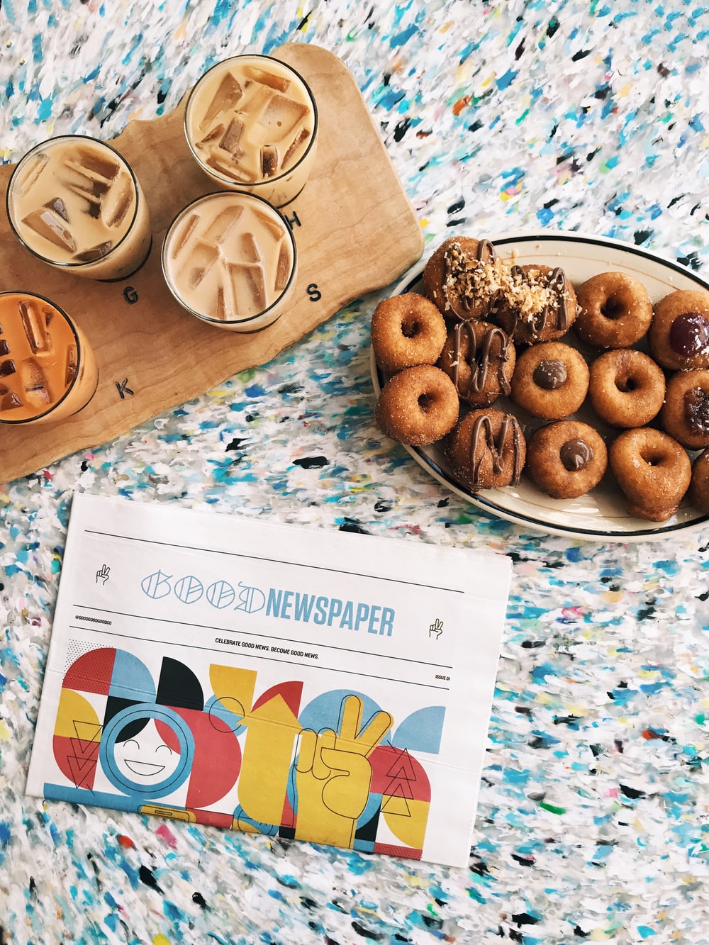 doughnuts on oval beige ceramic plate beside four glass cups on brown wooden board