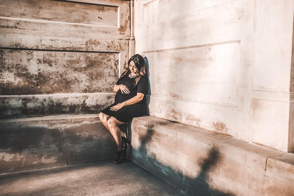 woman sitting on concrete pavemen