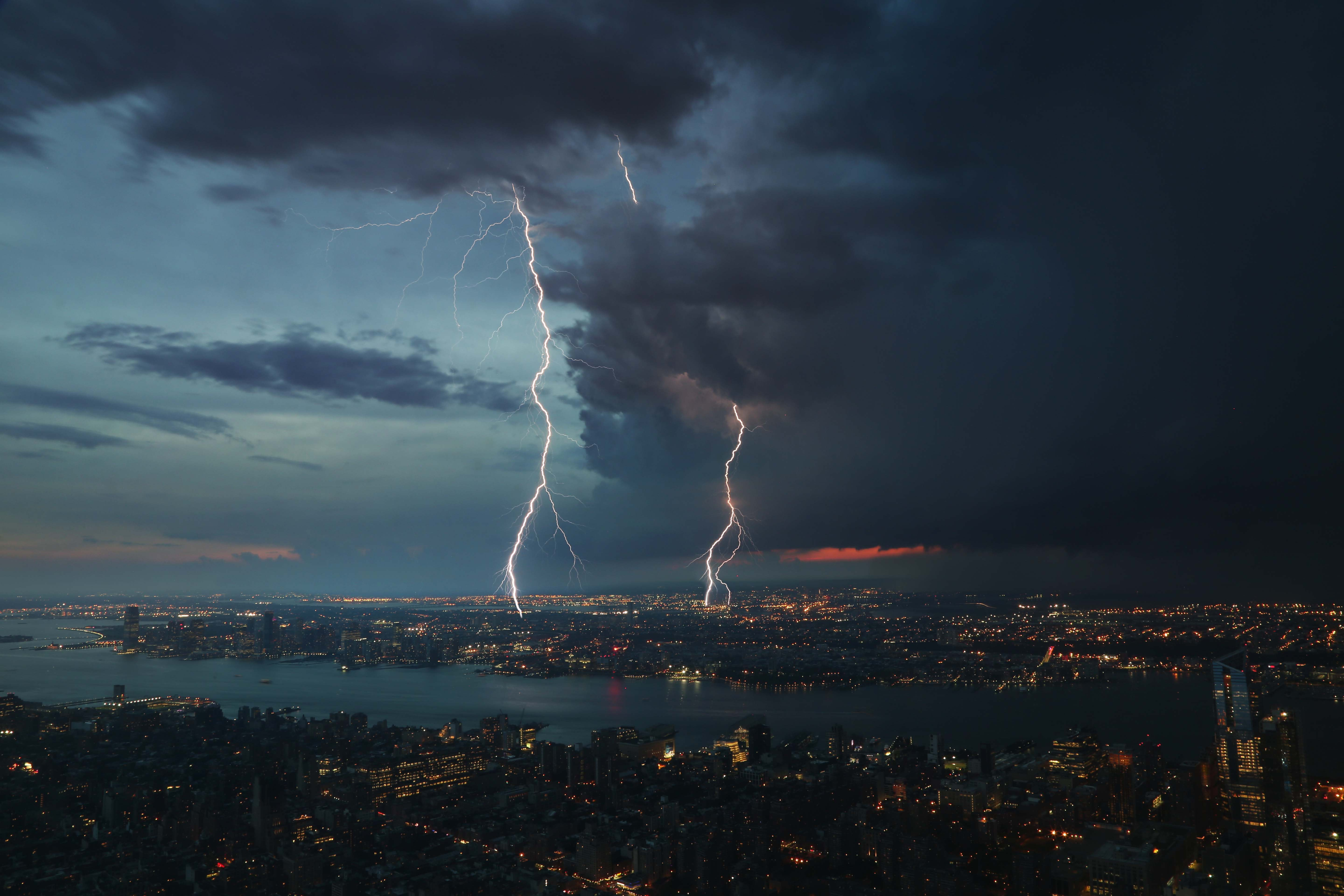 Large lightning strikes coming from the clouds into the city.