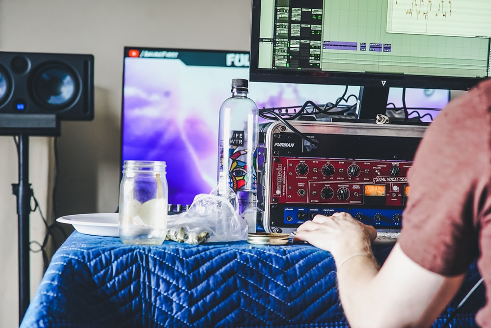person using computer beside clear glass bottle and jar on blue tablecloth