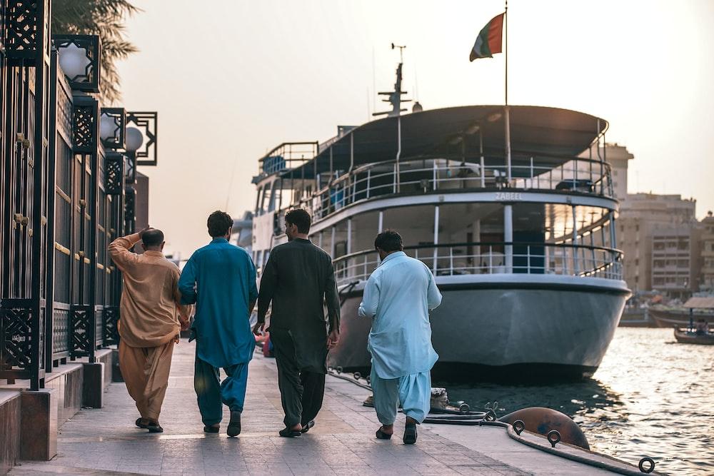 four men walking in front of ship