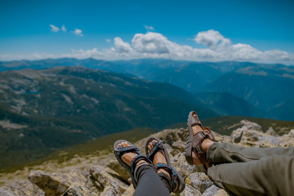 two person's feet cross leg on gray rocks