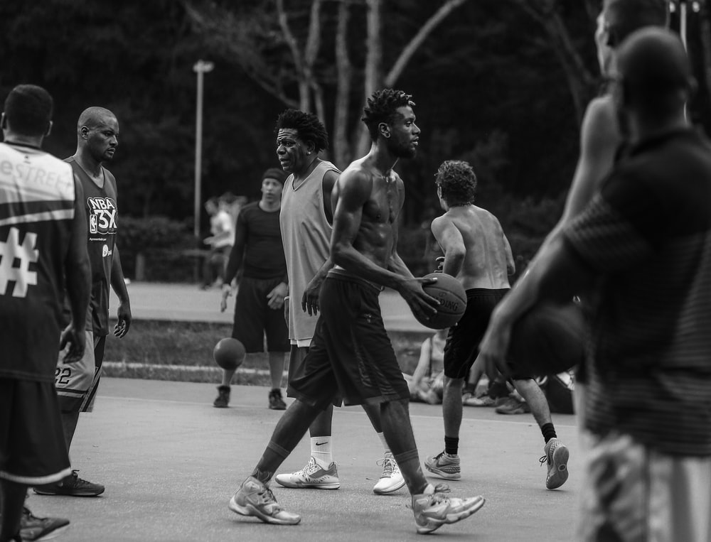grayscale photo of people playing basketball
