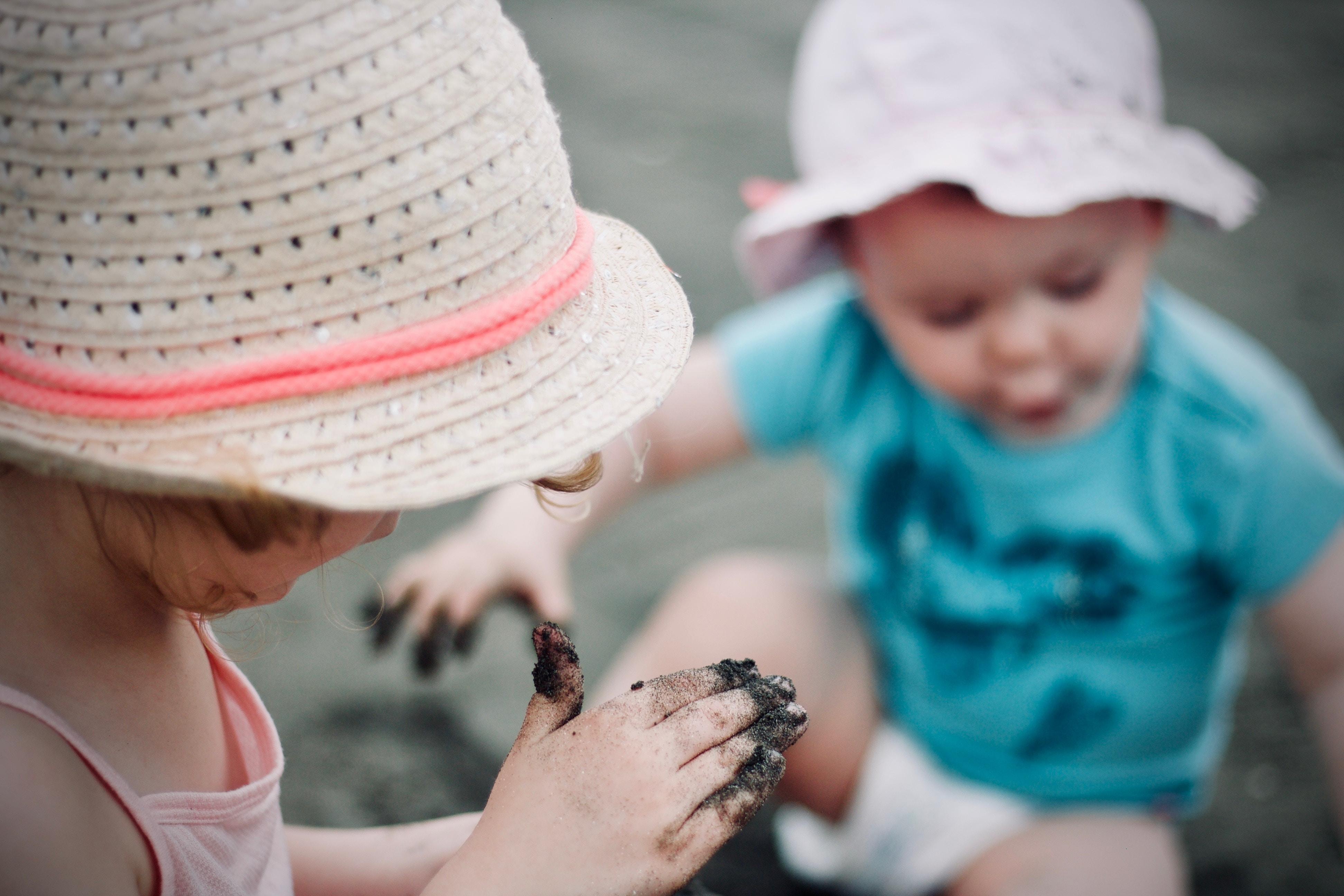 closeup photo of girl wearing sun hat holding sand