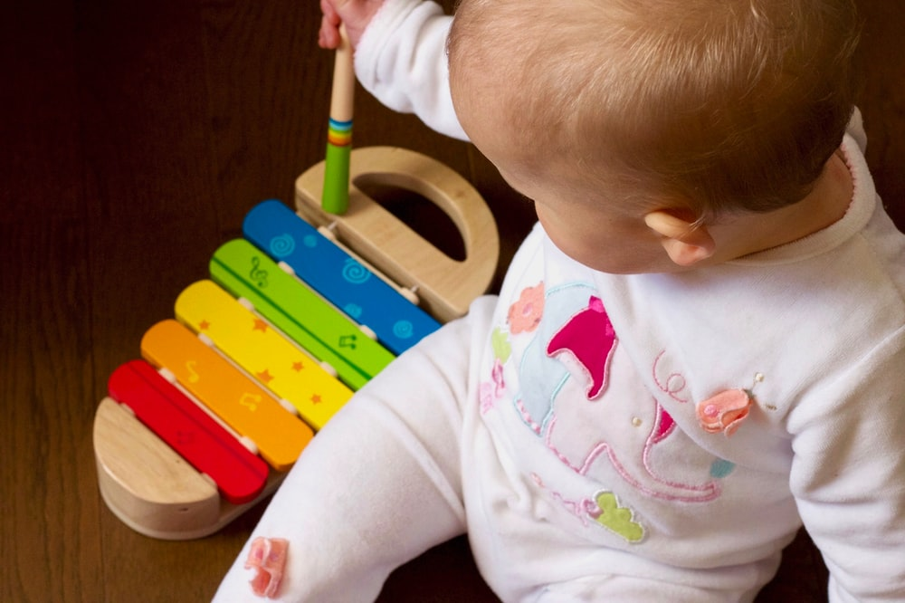 baby playing multicolored xylophone toy