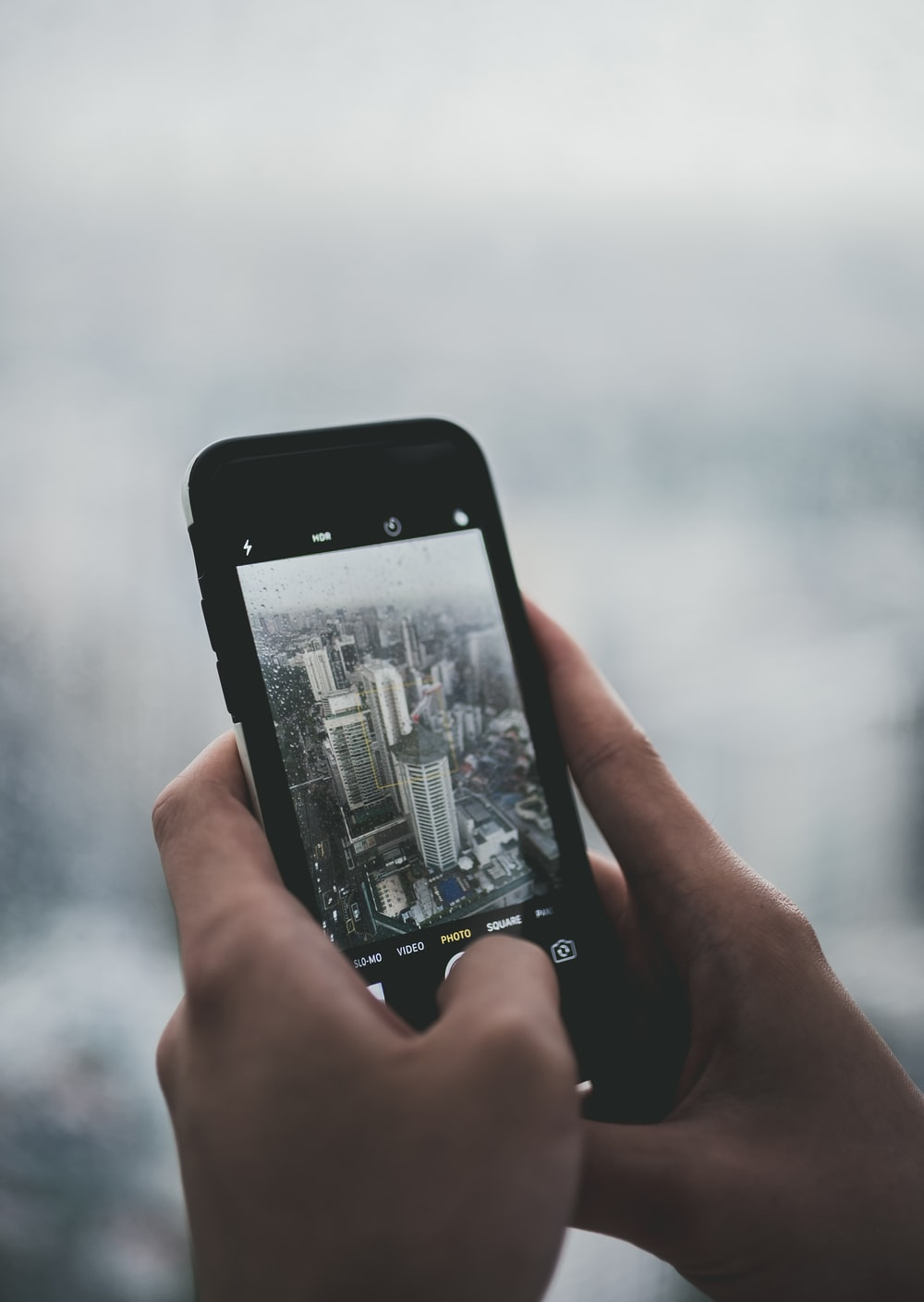 person holding black smartphone while taking photo of buildings