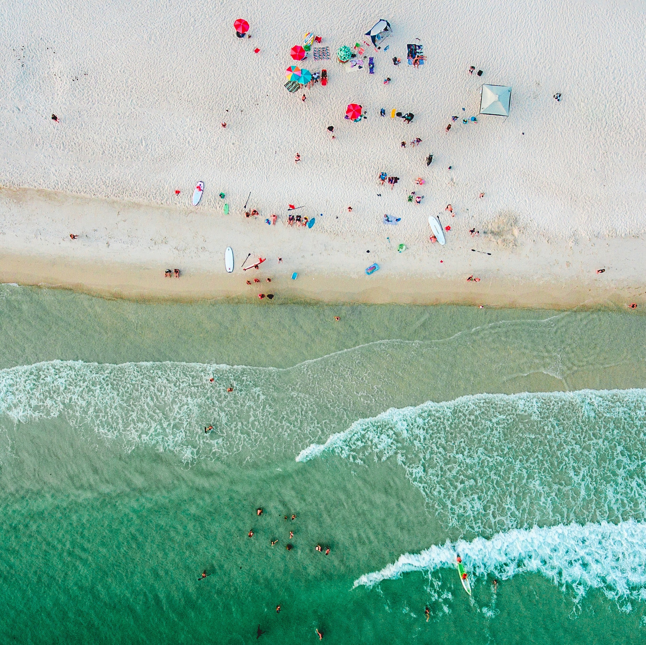 aerial photo of people on seashore and sea at daytime