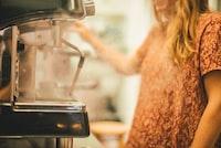 person in front of gray commerial espresso machine