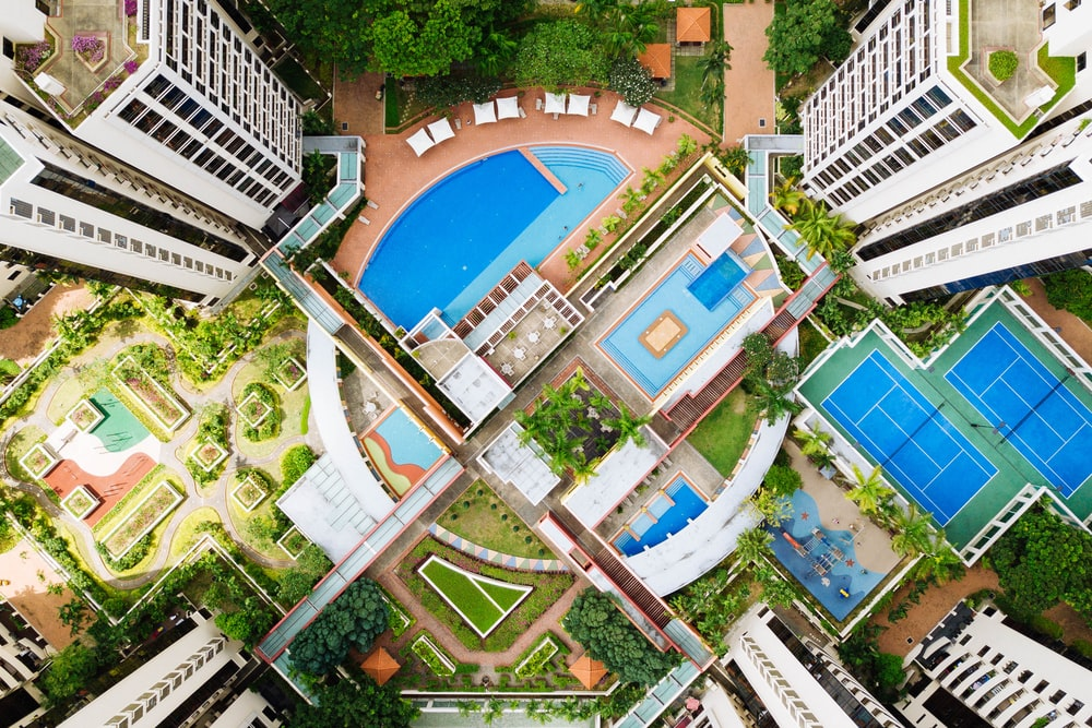 bird's-eye view photography of buildings with pools and tennis courts