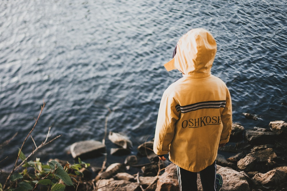person in yellow jacket standing on cliff