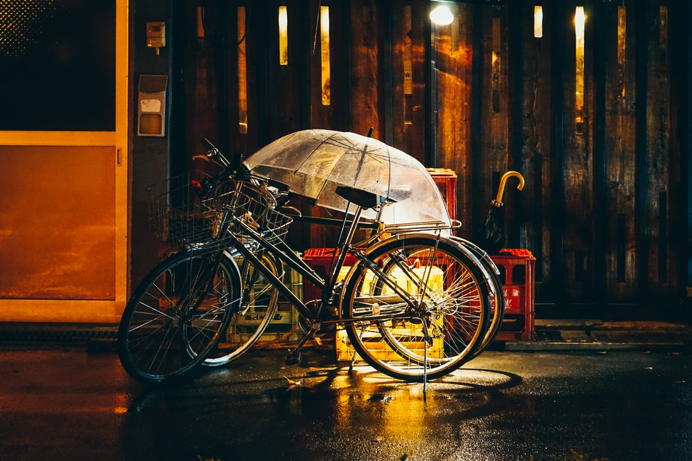 clear umbrella on black bicycles