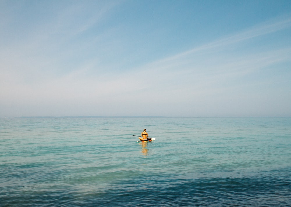 person in middle of body of water during daytime