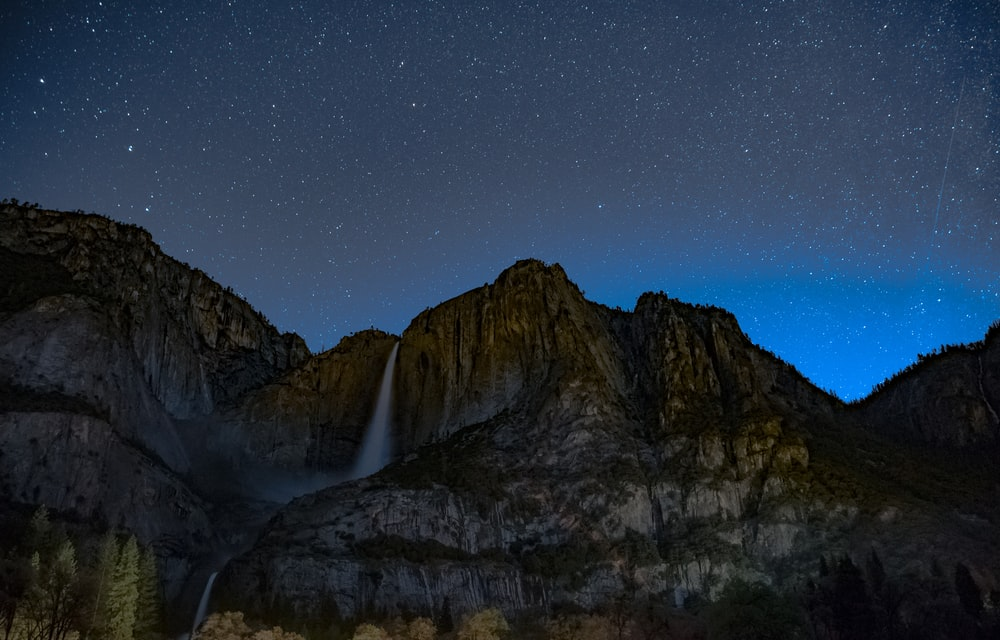 waterfalls on brown rugged mountain under blue sky at nighttime